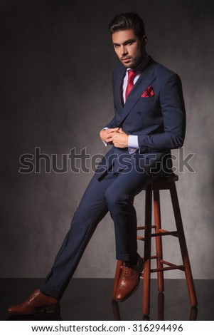 Full body of a handsome young business man looking at the camera while closing his jacket. - stock photo
