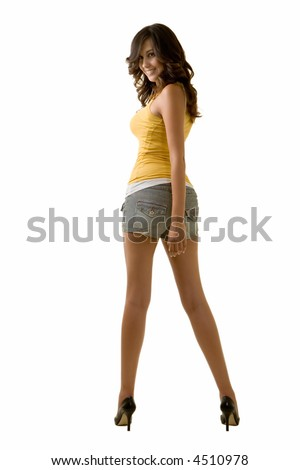 Full body of an attractive tall brunette woman with long sexy legs wearing shorts and yellow tank top looking back over shoulder standing on white background