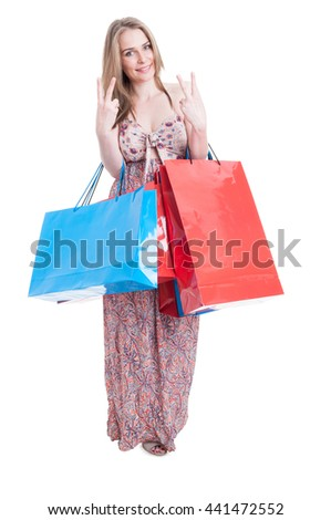 Full body of beautiful shopper female showing double peace symbol and carrying shopping bags isolated on white with copy space area