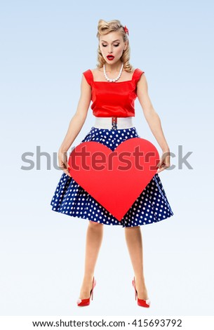 Full body of woman holding heart symbol, dressed in pin-up style dress with polka dot, on blue background. Caucasian blond model posing in retro fashion and vintage concept studio shoot. - stock photo