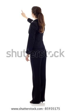 Full body of young business woman pointing at something from the back, isolated over white background - stock photo