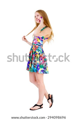 Full body of young teenager blonde girl in mix color dress speak by cell mobile phone, isolated on a white background - stock photo