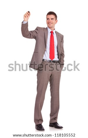 full body picture of a business man writing with marker and holding a hand in his pocket isolated on white background - stock photo
