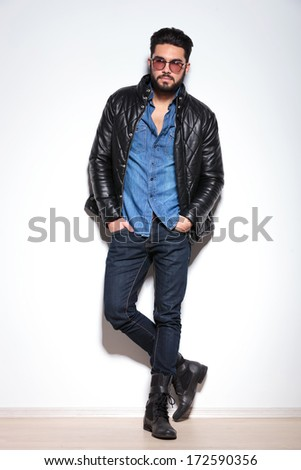 full body picture of a casual man in leather jacket, jeans and boots against studio wall - stock photo
