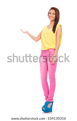 full body picture of a happy young casual woman showing something on the palm of her hand, against white background - stock photo