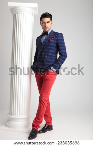 Full body picture of a smart casual fashion man holding one leg in front of the other and his hands in pockets. - stock photo