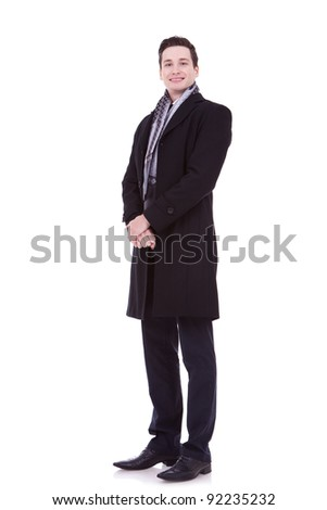 full body picture of a smiling young man in winter or autumn clothes on white background