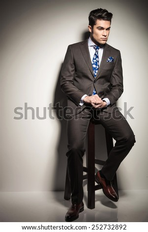 Full body picture of a young business man sitting on a stool while looking down thinking. - stock photo