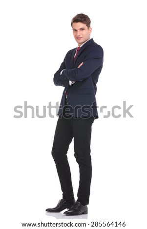 Full body picture of a young business man standing with his hands crossed. - stock photo
