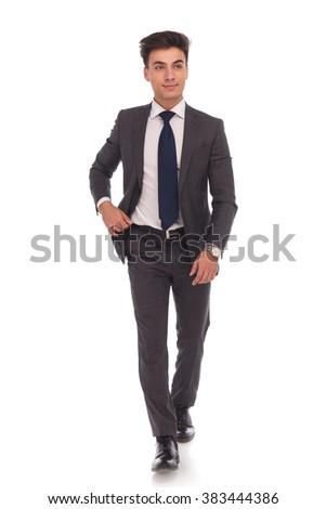 full body picture of a young business man walking and looking away from the camera on white studio background - stock photo