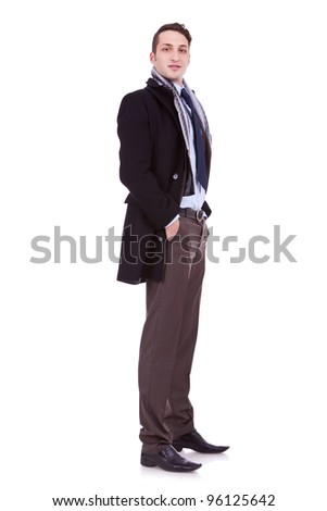 full body picture of a young business man with winter coat and with his hands in his pockets, over white background - stock photo