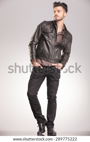 Full body picture of a young casual fashion man standing on studio background with his hands in pockets, looking away from the camera. - stock photo