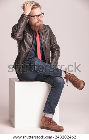 Full body picture of a young casual man sitting on a white cube, fixing his hair while looking away from the camera. - stock photo