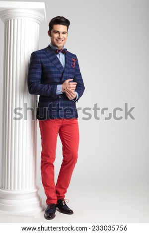 Full body picture of a young casual man smiling for the camera, near a white column on studio background. - stock photo