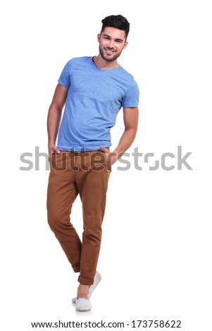 full body picture of a young casual man standing with hands in pockets and smiles - stock photo