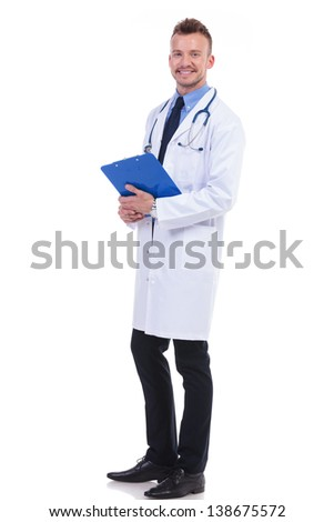 full body picture of a young doctor holding his notepad and  looking at the camera - stock photo