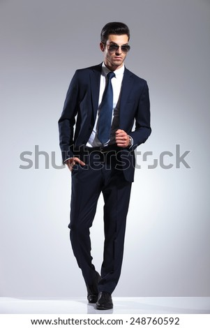 Full body picture of a young elegant business man pulling his jacket while holding one hand in his pocket. - stock photo