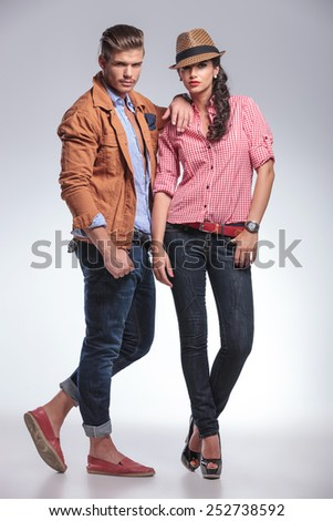 Full body picture of a young fashion couple posing on grey studio background, the man is leaning on the woman. - stock photo