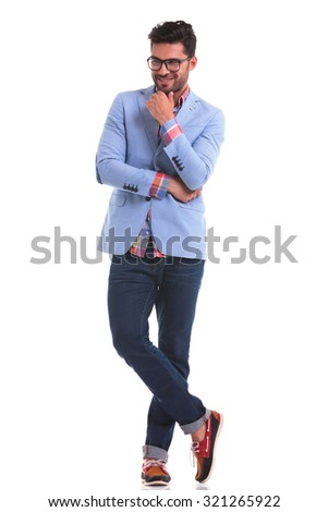 Full body picture of a young fashion man standing with his legs crossed smiling away from the camera. - stock photo
