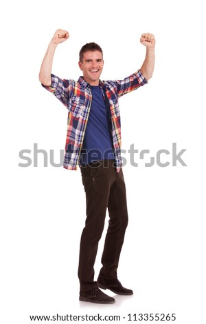 Full body picture of an excited casual young man cheering with his hands raised in the air, isolated on white background