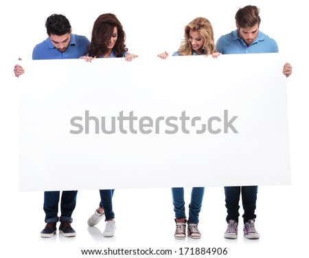 full body picture of casual people holding and looking at a blank board on white background - stock photo
