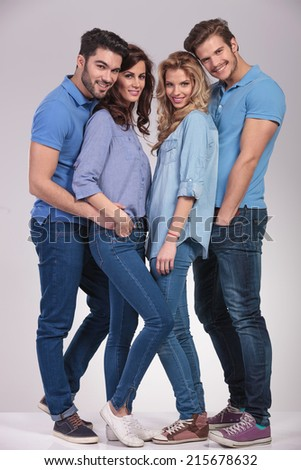 full body picture of four happy casual young people standing together and smile on grey studio background - stock photo