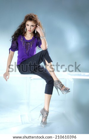Full body portrait fashion model sitting cube on light background - stock photo
