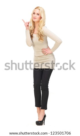 Full body portrait of a beautiful girl pointing her finger up. Isolated on white background. Possibility for copy space - stock photo
