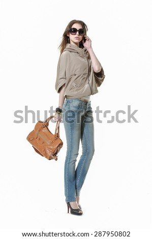 Full body portrait of a beautiful young woman in jeans with bag ,sunglasses posing - stock photo