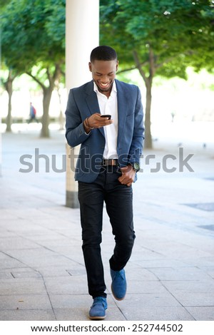 Full body portrait of a handsome man walking and sending text message on cellphone - stock photo