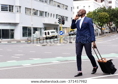 Full body portrait of a happy businessman walking with a bag and talking on mobile phone - stock photo