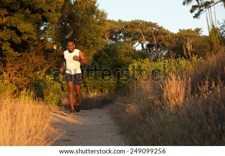 Full body portrait of a healthy young black man jogging outdoors - stock photo