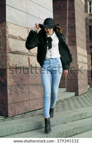 Full body portrait of a young beautiful lady walking at street of  the old city. Model wearing stylish black fur coat and wide-brimmed hat. Female fashion concept. Toned - stock photo