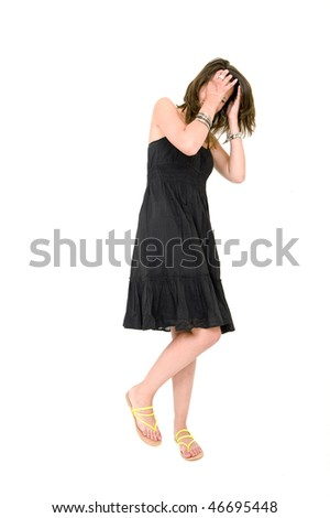 Full body portrait of a young brunette woman in a black summer dress, covering her head with her hands, laughing, and very much self-aware - stock photo