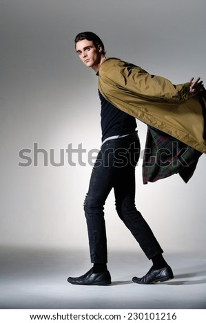 Full body portrait of a young fashion male walking on light background - stock photo