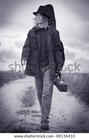 Full body portrait of a young musician walking on the field - stock photo