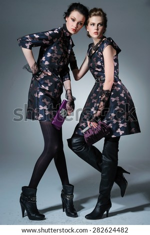 Full body portrait of a young two woman with a purse posing - stock photo