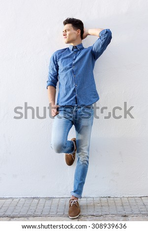 Full body portrait of an attractive male fashion model posing against white background - stock photo
