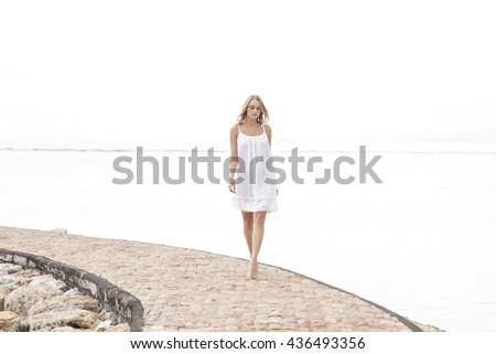 full body portrait of an attractive woman walking on the beach enjoying summer - stock photo