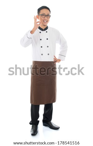 Full body portrait of Asian chef showing tasty and satisfied hand sign , smiling and standing isolated on white background. - stock photo