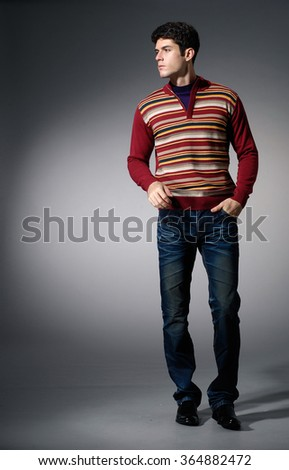 Full body portrait of casual young man in studio - stock photo
