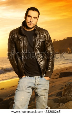 Full body portrait of good looking man in golden light wearing a leather jacket against beautiful sunset - stock photo