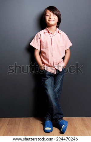 full body portrait of handsome little boy smiling with hands in his pockets - stock photo