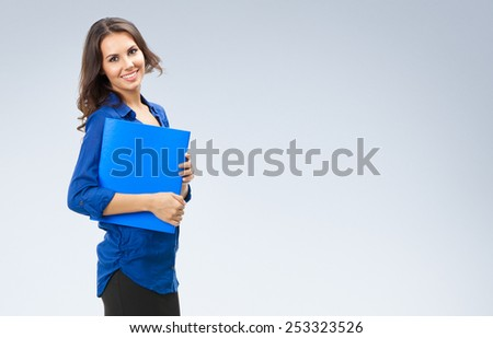 Full body portrait of happy smiling business woman with blue folder, with copyspace area - stock photo