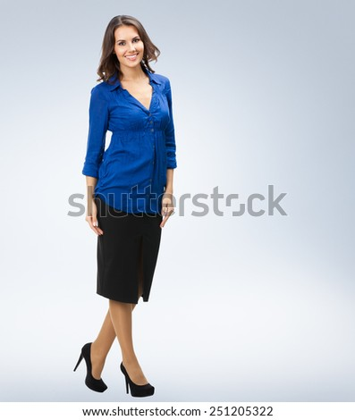 Full body portrait of happy smiling young business woman, with copyspace area - stock photo