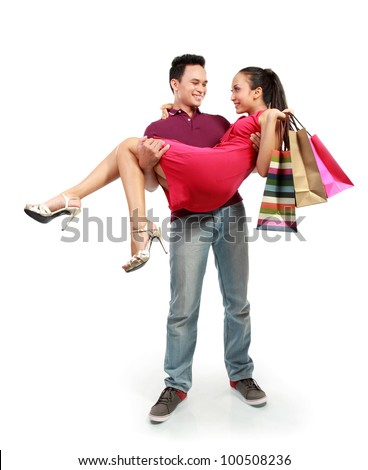full body portrait of happy young man carrying his girlfriend with many shopping bags - stock photo