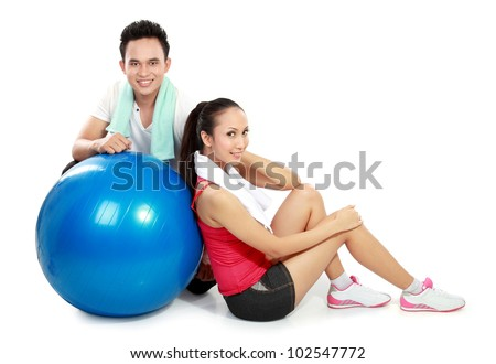 full body portrait of sporty couple with pilates ball isolated on white background - stock photo