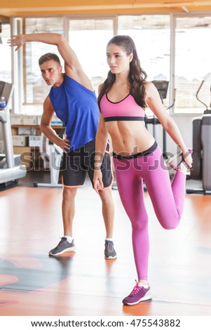 full body portrait of two sporty people doing stretching before workout at the gym