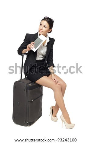 Full-body portrait of young business woman sitting on her black travel bag and holding the tickets with passport isolated on white background