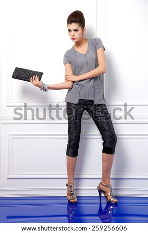 Full body portrait of young fashion model  holding purse posing in studio - stock photo